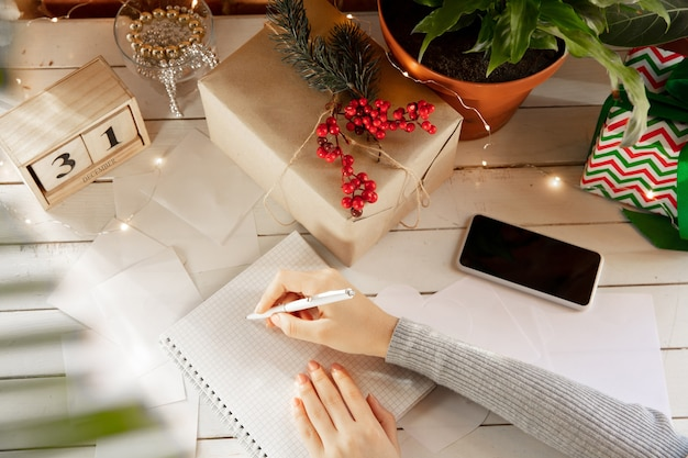 Writes wishes dreams of goals plans make a list for writing in notebook female hands