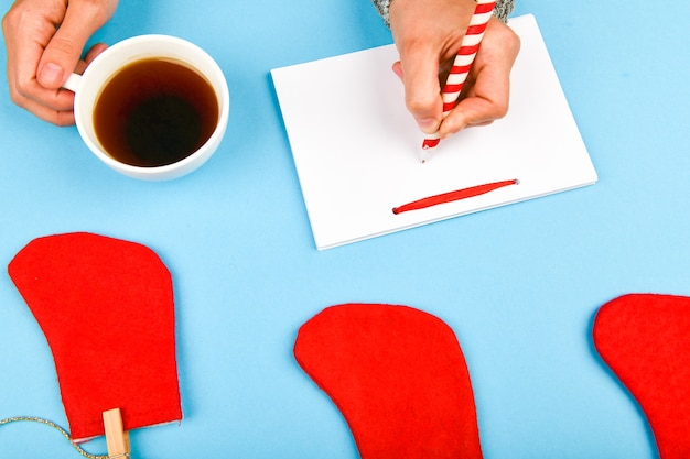 Writes wishes with a coffee mug. dreams of goals plans make a list for writing new year christmas concept in notebook