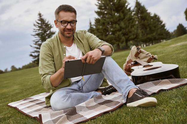 Написание песни молодой творческий человек в очках сидит на зеленой траве в парке и делает