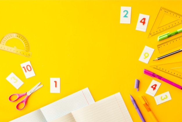 Writing-books, pens, pencils, numbers and rulers on a yellow background