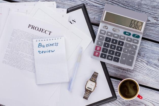 비즈니스 리뷰를 작성합니다. 나무 테이블에 계산기와 커피 한 잔이 있는 비즈니스 프로젝트. 상위 뷰 플레이 레이.