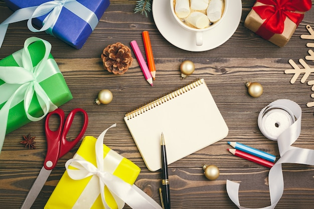 Writing christmas greeting cards open notepad with pen on decorated wooden table