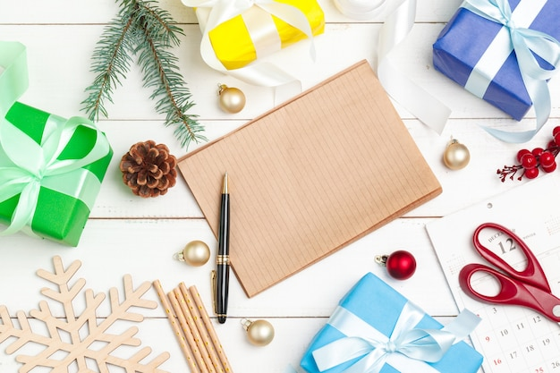 Writing christmas greeting cards. open notepad with pen on decorated wooden table