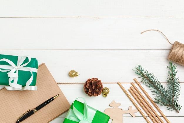 크리스마스 인사말 카드 쓰기 장식된 나무 테이블에 펜으로 메모장을 엽니다 프리미엄 사진