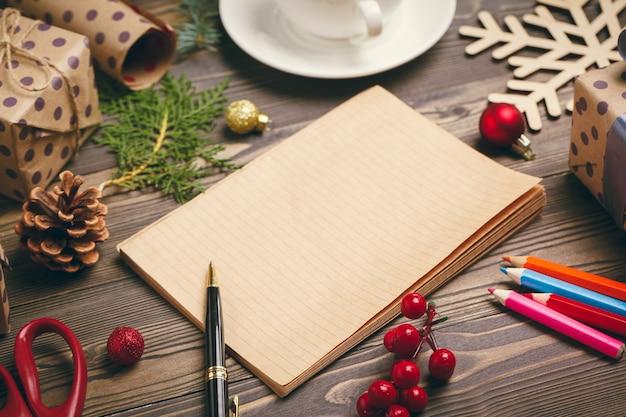 크리스마스 인사말 카드 쓰기 장식된 나무 테이블에 펜으로 메모장을 엽니다