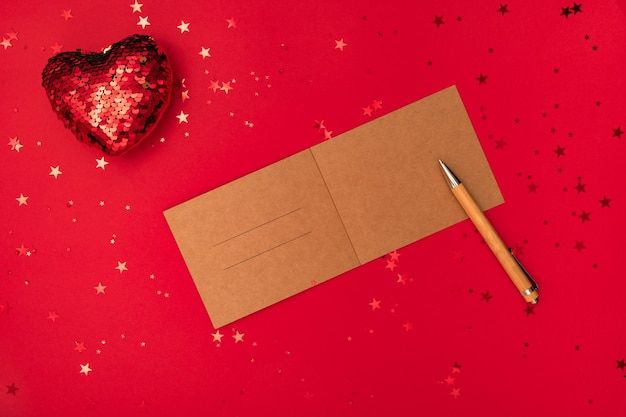 Writing a christmas letter with congratulations or congrats, pen and decorations on red surface
