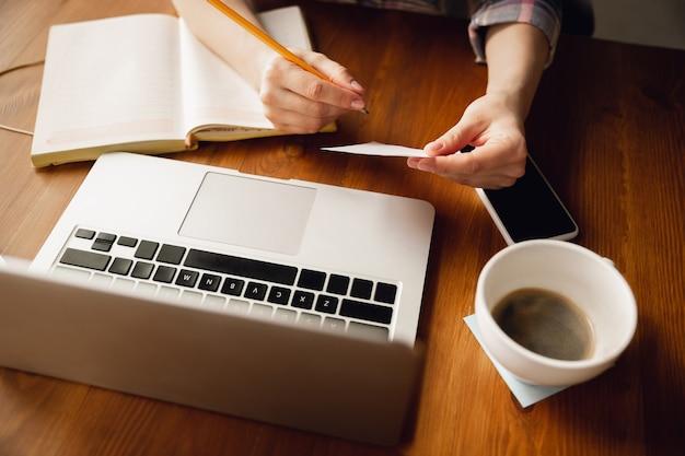 Scrittura. primo piano di mani femminili caucasiche, lavorando in ufficio. concetto di affari, finanza, lavoro, acquisti online o vendite. copyspace. formazione, comunicazione freelance.