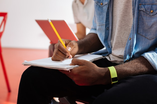 Writing. close up of the hands of a young student sitting at the lecture and making necessary notes in his notebook