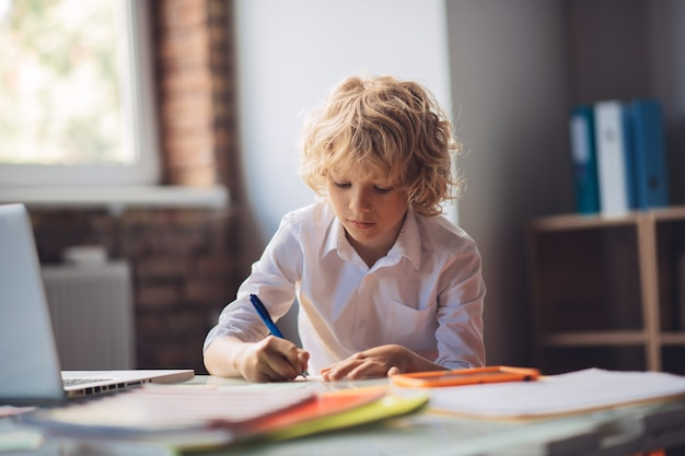 書き込み。テーブルに座って書くかわいい金髪の少年