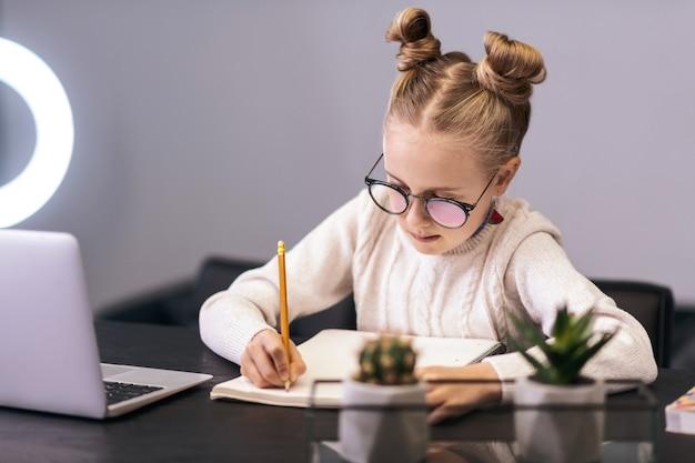 書き込み。ノートに何かを書いている白いセーターを着ているかわいい青い目の長い髪の少女