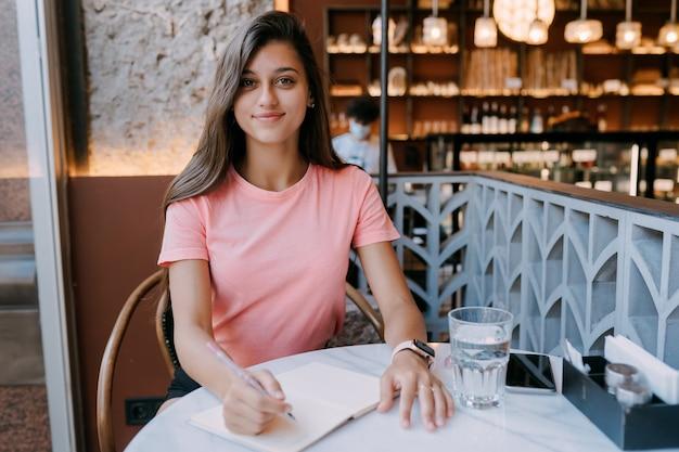 커피 숍에서 메모에 유제품을 쓰고, 삶의 기억으로 개념. 커피 숍에서 여자입니다. 메모 메모장을 만드는 웃는 여자.