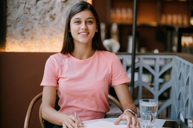 커피숍에서 유제품을 메모에 쓰고, 인생의 기억으로 개념. 커피숍에서 여자입니다. 메모장을 만드는 웃는 여자.