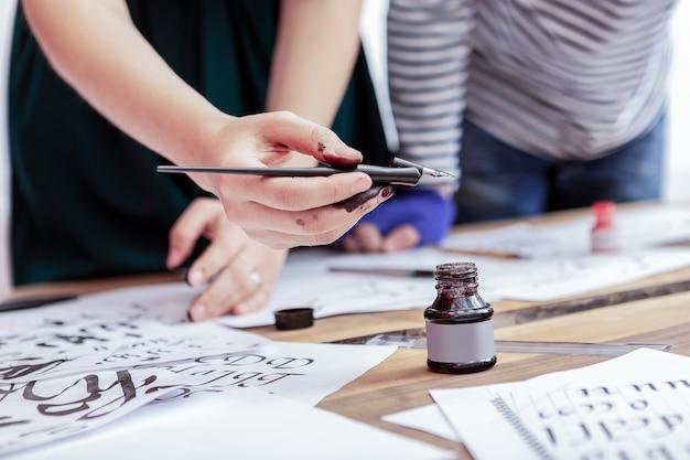 インクで書く。インクで書いた後、汚れた手を持っている手を身に着けている若い有望な女性アーティスト
