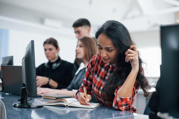 メモ帳に書き込みます。近代的なオフィスで働くカジュアルな服装の若い人たちのグループ