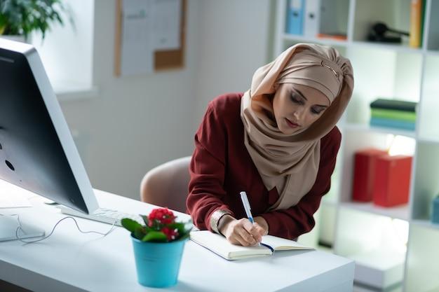 ノートに書き込む。作業中にノートに書き込みヒジャーブを身に着けている美しい若いイスラム教徒の女性