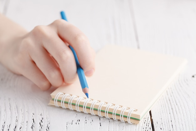Writing memories note, close up female hand with pen