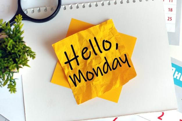 しわくちゃの黄色い紙に書く:こんにちは月曜日。焦点ぼけ。黒い文字。デスクオフィスの拡大鏡と緑の鉢植え。