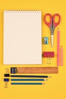 Блокнот и школьные принадлежности плоской планировки. фото высокого качества