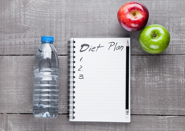 Writing pad with apples and water as diet  idea on wooden board