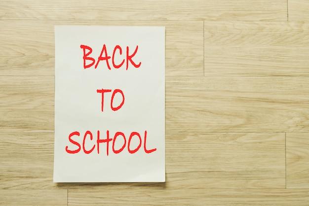 木製の背景の上に学校のテキストに戻って紙を書く。