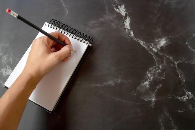 Написание карандаша в блокноте на черном мраморе выборочный фокус