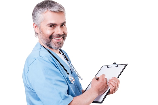 Rx 처방전을 작성합니다. 카메라를 보고 웃고 있는 성숙한 의사의 옆모습