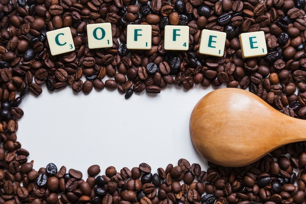 Scrittura e cucchiaio su chicchi di caffè