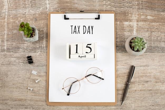 木の立方体で税の日を書く4月15日紙、眼鏡、ペンをデスクトップに。