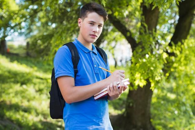 Writing teen boy looking at camera intently
