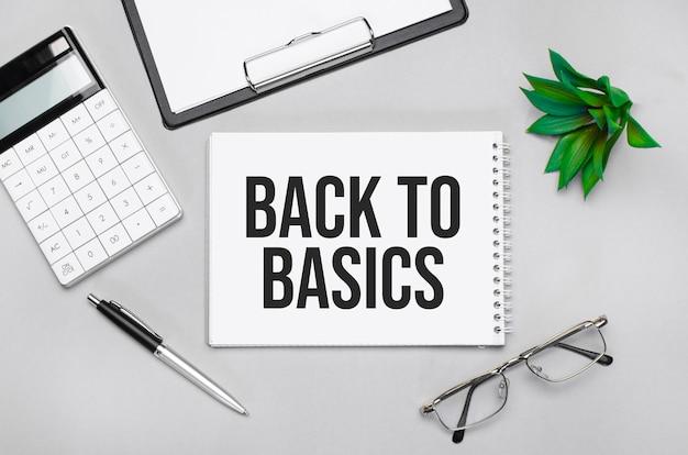 Back tobasicsを示すテキストを書く。電卓、ペン、プラン、メガネ、灰色の背景に黒いフォルダー