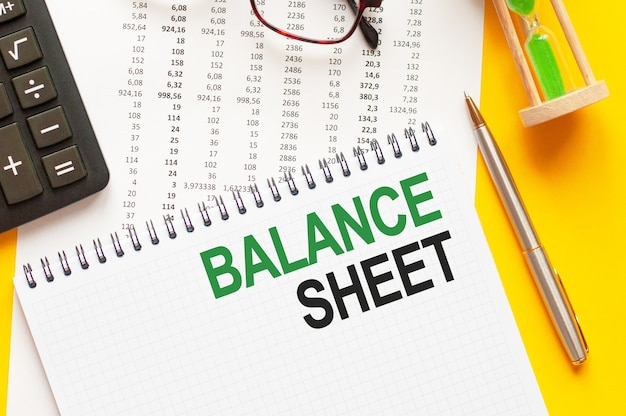 Writing text showing balance sheet. writing text balance sheet on white paper card, green and black letters, yellow wall. business concept.