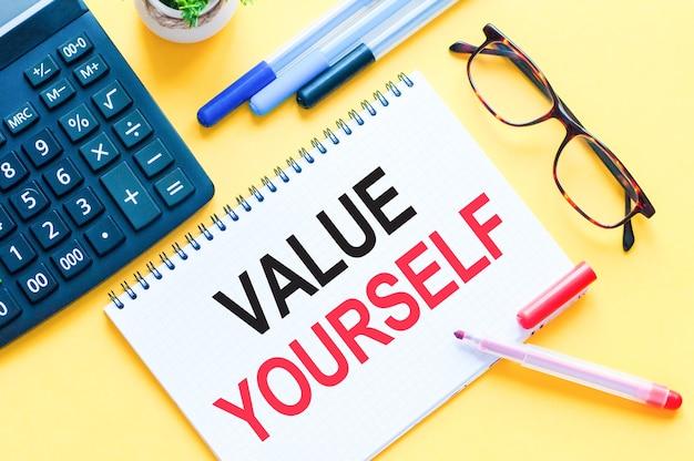 Valueyourselfを示すテキストを書く。ホワイトペーパーカード、赤と黒の文字に単語テキストvalueyourself。教育のためのビジネスコンセプト。