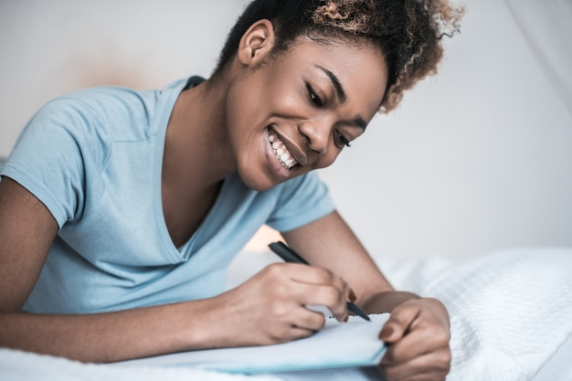 Writing thoughts. smiling young adult african american woman writing with pen in notebook lying on stomach on bed