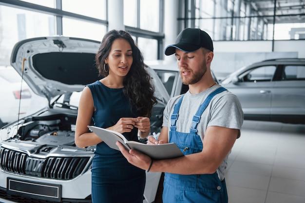 Scrivere usando la penna. donna nel salone dell'auto con il dipendente in uniforme blu che riprende la sua auto riparata