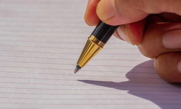 Writing with a gold pen on  white paper, selected focus