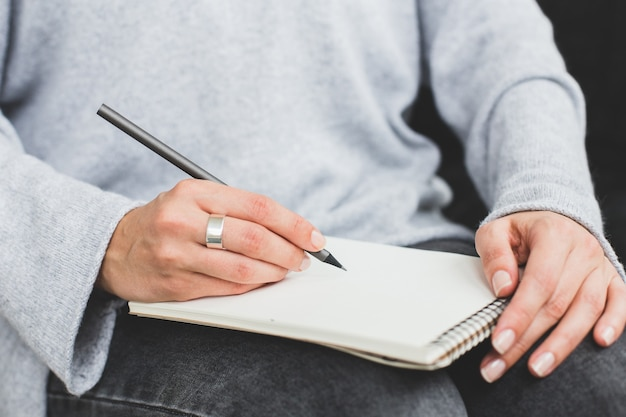 Пишущая женская рука делает заметки в бумажной записной книжке. закройте вверх.