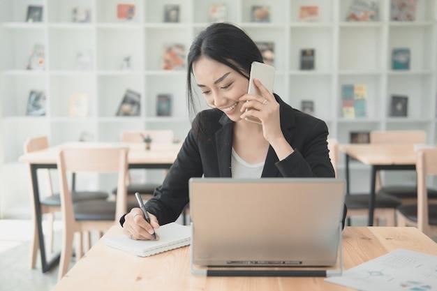 情報データをリストするための携帯電話とwritng文書と話しているプロの働く女性。技術コンセプトをオフィスで働いています。