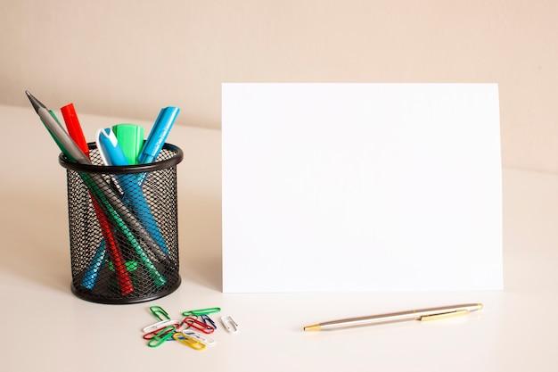 テーブルの上の白い折り畳まれた紙に書かれています。近くにはペンと鉛筆があります。ビジネスコンセプト。