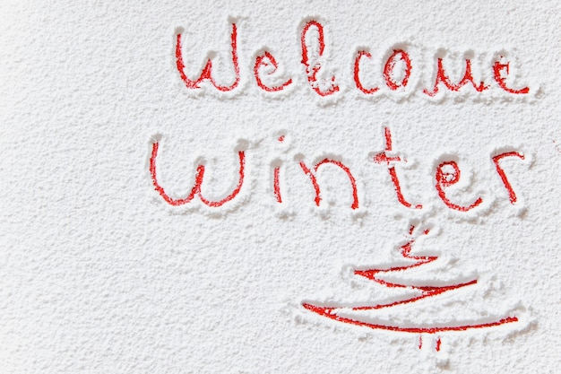 Written welcome winter on the snowy background