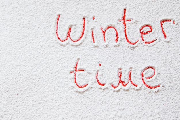 Written winter time on the snowy backgroun