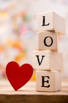 Written on wooden blocks love and red heart