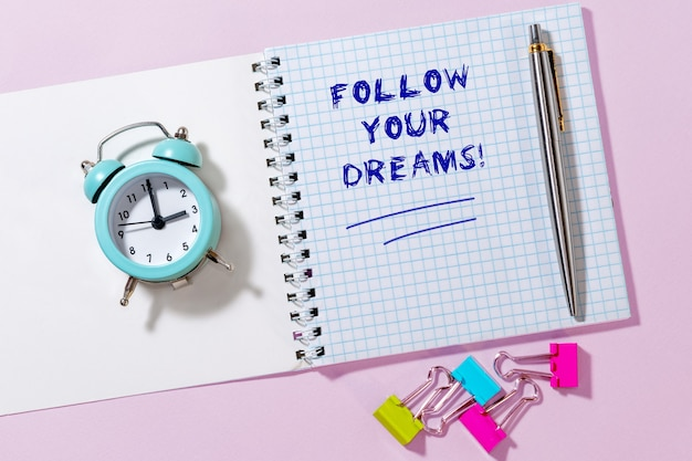 Written words in notepad follow your dreams. top view of notepad and retro alarm clock.