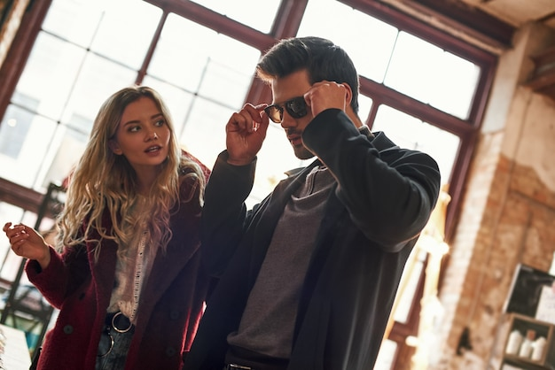サングラスのサイズが間違っています。小さなストリートマーケットで男性用のサングラスを選ぶ幸せな若い楽しいカップル。サングラスをかけている若い男と彼のガールフレンドの意見を聞く