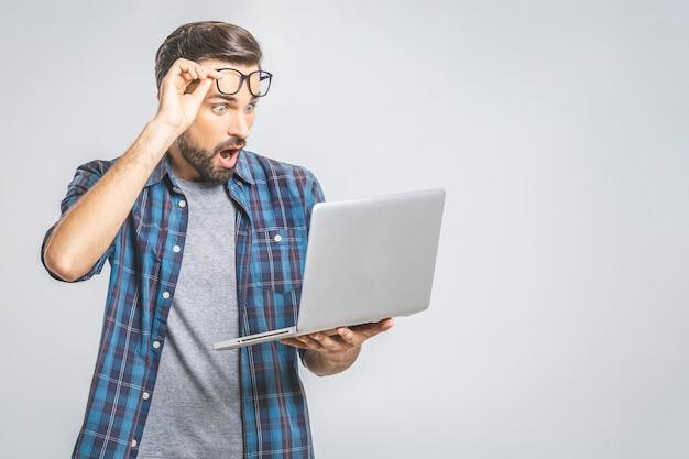 Wtf ?! о, мой бог! о нет! молодой изумленный эмоциональный брюнет с щетиной с грустной гримасой смотрит на экран устройства