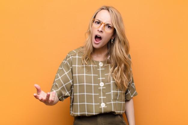 怒っている、イライラして欲求不満の叫びwtfを探している若いかなりブロンドの女性またはフラットカラーの壁に対して何が問題なのか