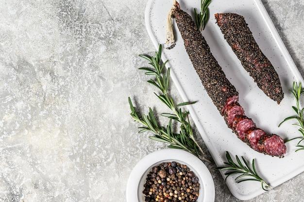 Wurst, fuet, нарезанная колбаса. свиная колбаса. серый фон вид сверху. пространство для текста