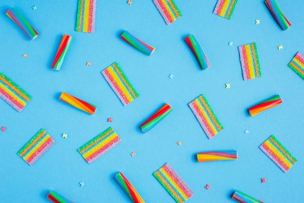青色の背景にパターンwuth虹キャンディー、トップビューフラットレイアウト