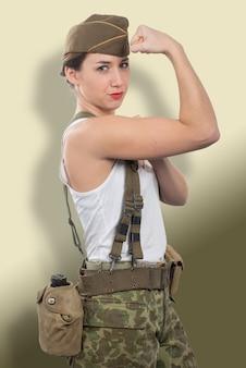 Молодая женщина, одетая в американскую военную форму ww2, показывает бицепс