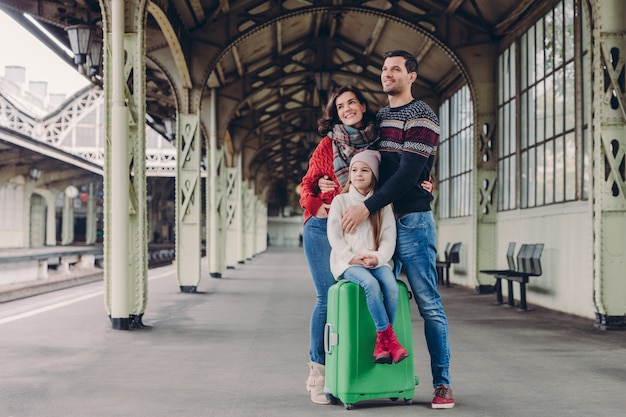 Wwife and husband cuddle with love, their daughter sits at suitcase, pose together on platform.