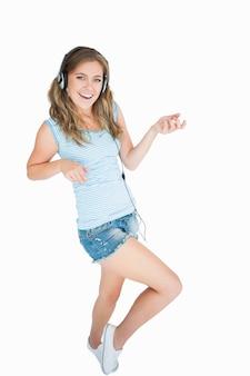Wwomanはヘッドフォンで音楽を楽しんで、エアギターを弾く